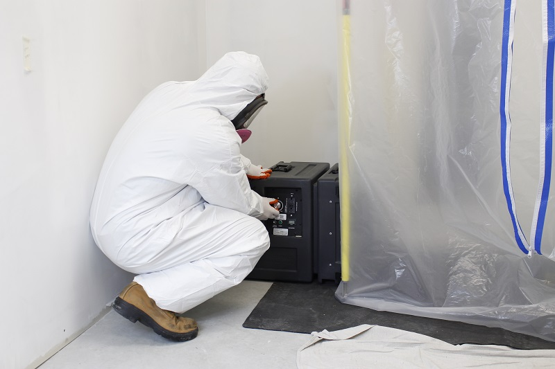 Fan Coil Removal - Technician with HEPA Vacuum and Plastic Tent